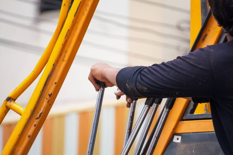 construction worker controls of lifting crane in crane truck